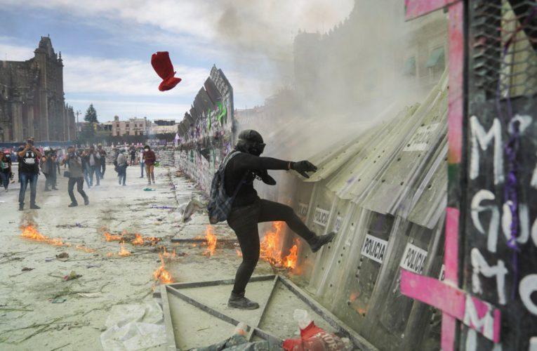 Mujeres logran tirar algunas vallas instaladas en el Palacio Nacional
